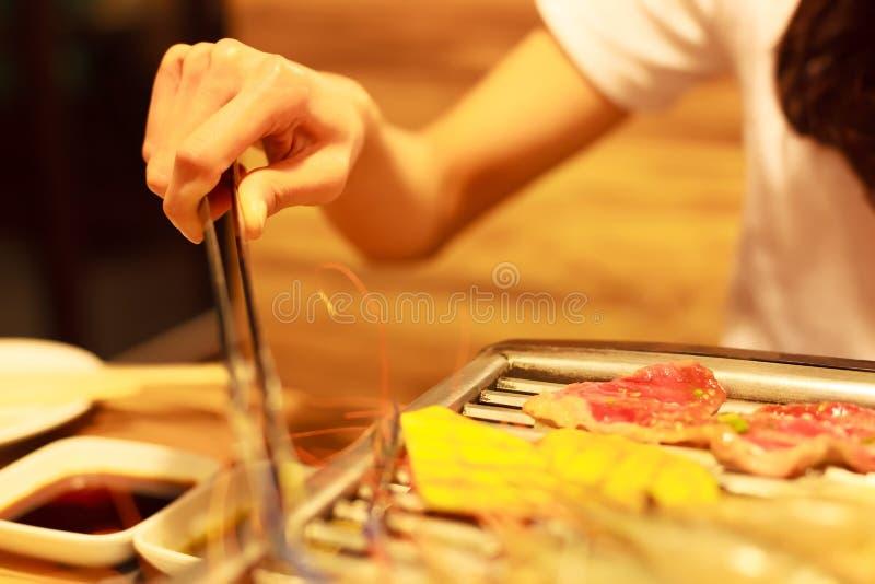 Kobiety ręki mienia stali nierdzewnej tong gorący karmowy porywający kahat smaży mięsnego i jarzynowego jedzenie na grilla grilla zdjęcie royalty free