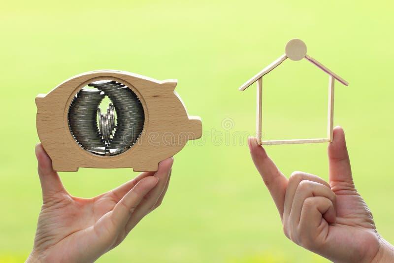 Kobiety ręki mienia sterta moneta pieniądze w prosiątko banka mienia i drewna drewnianym domu na naturalnym zielonym tle, oszczęd zdjęcie royalty free