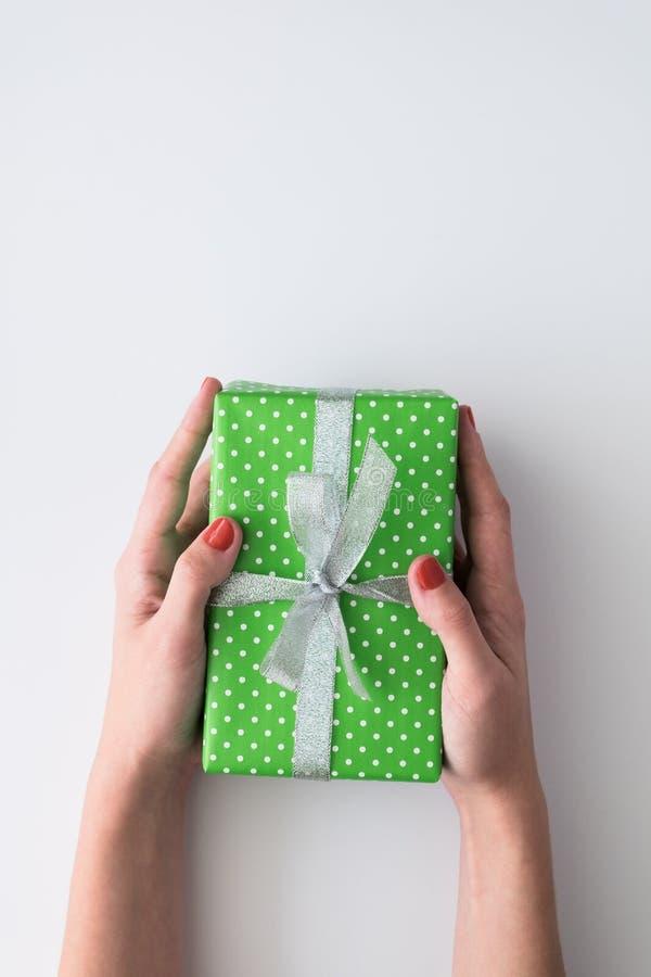 Kobiety ręki mienia zieleni prezenta pudełko odizolowywający na białym tle Odgórny widok, mieszkanie nieatutowy Copyspace obrazy stock