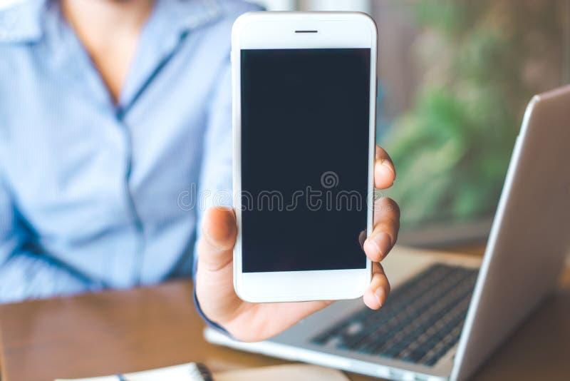 Kobiety ręki przedstawienie biały telefon komórkowy przy pustym ekranem w th obrazy stock