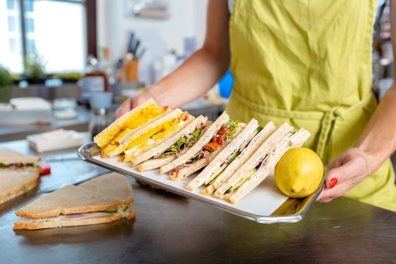 Kobiety ręki przewożenia kanapka w tacy zdjęcie royalty free