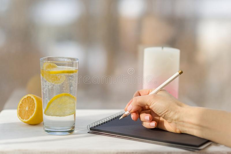 Kobiety ręki remisy w projektanta czerni notatniku Tła okno, szkło woda mineralna z cytryną fotografia stock
