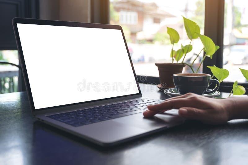 Kobiety ręki używać laptopu touchpad z pustym białym desktop ekranem z filiżanką na drewnianym stole i dotykający w kawiarni zdjęcia stock