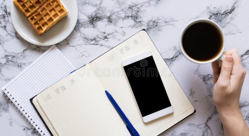 Kobiety r?ka, fili?anka kawy, planistyczny dzie?, biznesowy lunch i smartphone, fotografia royalty free