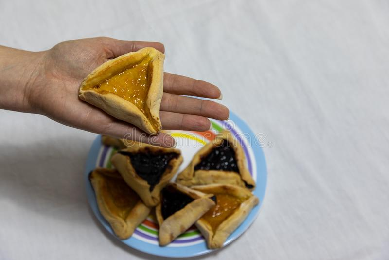 Kobiety r?ki mienia hamantash ciastko na g?rze kolorowego talerza z wi?cej hamantash ciastkami obrazy stock