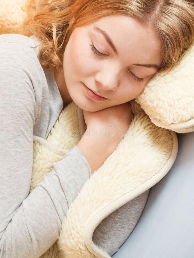 Kobiety relaksujący drzemanie w łóżku pod wełny koc fotografia stock