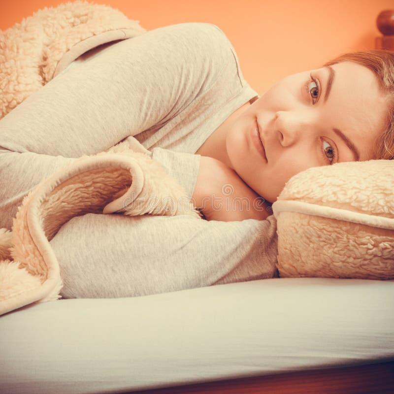 Kobiety relaksujący drzemanie w łóżku pod wełny koc zdjęcia royalty free