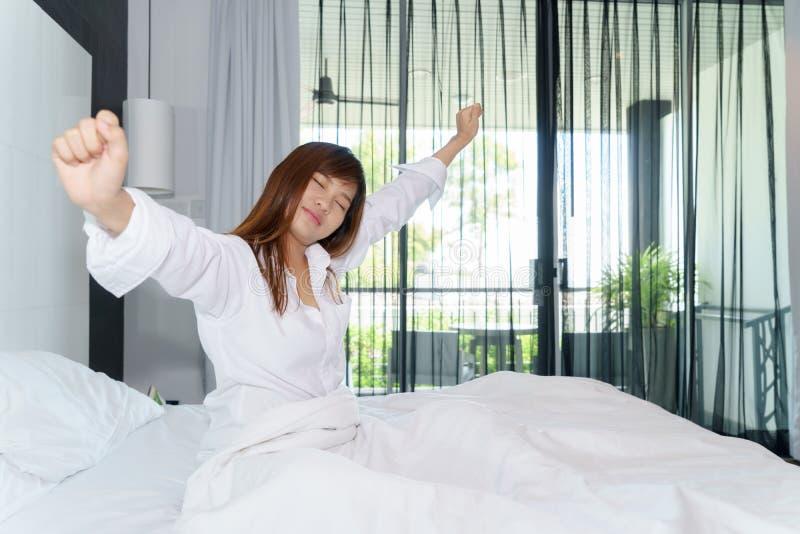 Kobiety rozciąganie i siedzący puszek na łóżku podczas gdy budzący się up wewnątrz zdjęcia royalty free