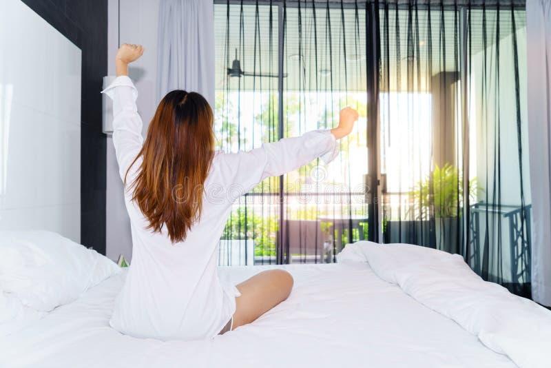 Kobiety rozciąganie i siedzący puszek na łóżku podczas gdy budzący się up wewnątrz zdjęcie royalty free