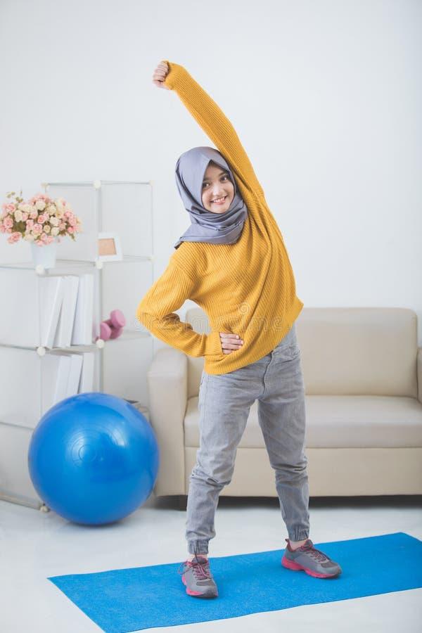 Kobiety rozciąganie podczas gdy robić ćwiczeniu w domu zdjęcie royalty free