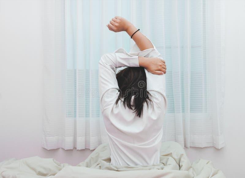 Kobiety rozciąganie w łóżku tylny widok, po budzić się up, obrazy stock