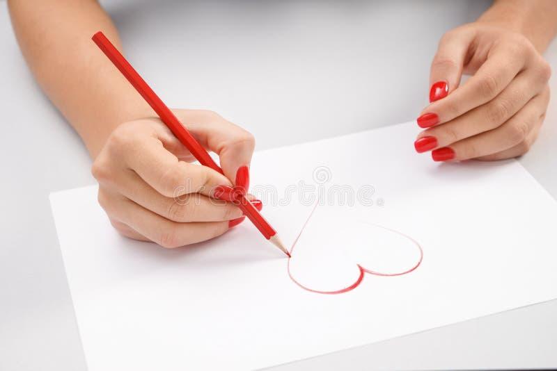 Kobiety rysunkowy serce na prześcieradle papier zdjęcia stock