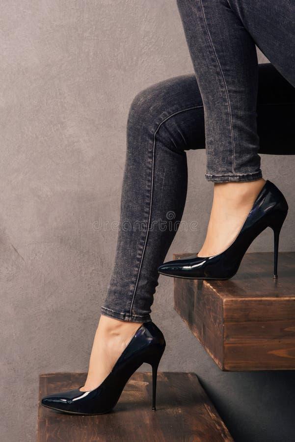 Kobiety ` s iść na piechotę w cajgach i heeled patentowych rzemiennych butach na drewnianej wspornik drabinie zdjęcie stock