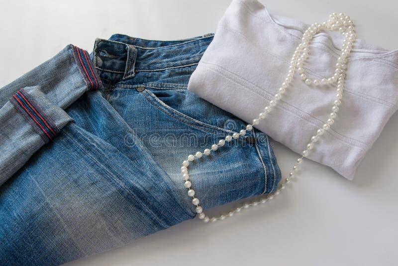 Kobiety ` s modny przypadkowy strój niebiescy dżinsy, biały pulower i biel perełkowa kolia -, obraz royalty free