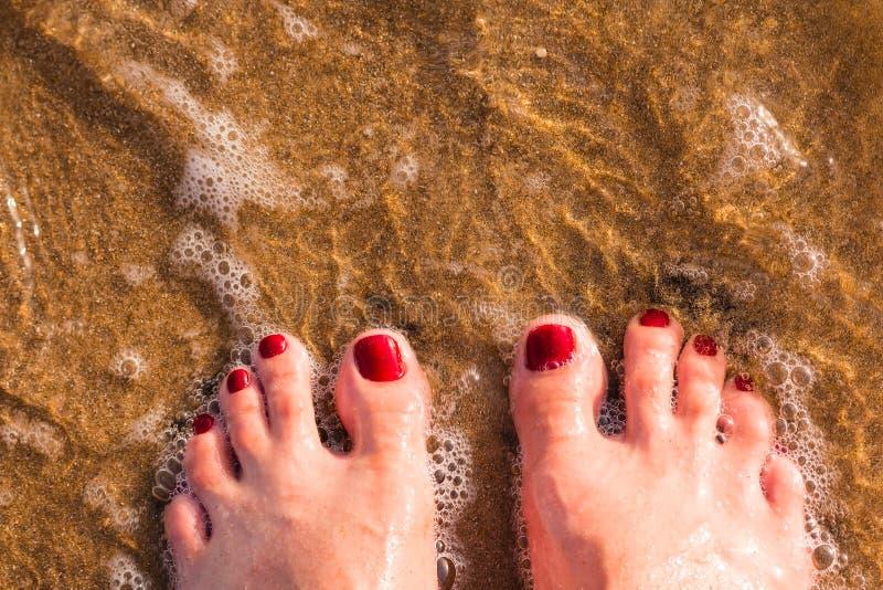 Kobiety ` s nogi, nadzy cieki stojaka na piasku przy plażą, cześć lata powitania wakacje pojęcie od wierzchołka palec u nogi obra obraz royalty free