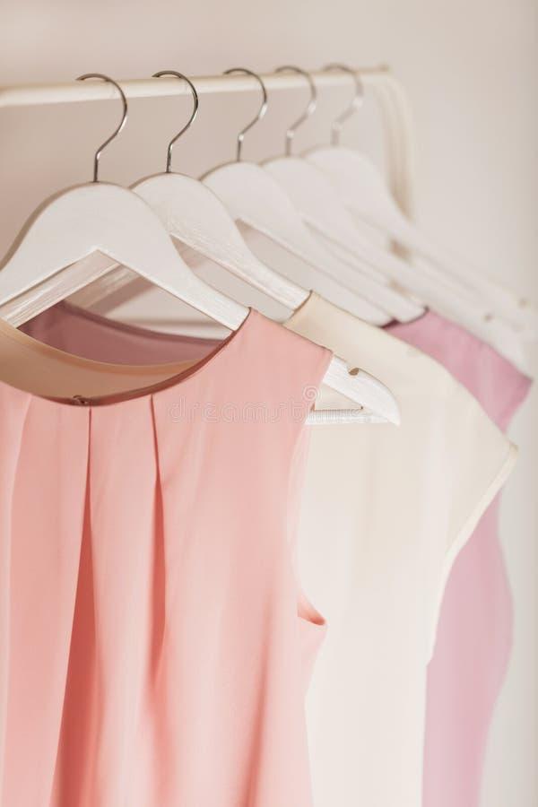 Kobiety ` s odzież w menchiach tonuje na białym wieszaku fotografia stock