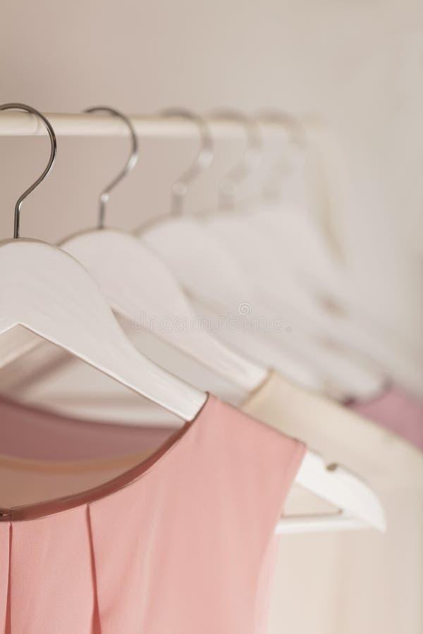 Kobiety ` s odzież w menchiach tonuje na białym wieszaku obraz royalty free