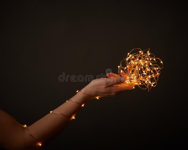 Kobiety ` s ręka dekoruje z żółtymi girlandami wokoło czarnego tła z kopii przestrzenią Boże Narodzenia zdjęcie royalty free