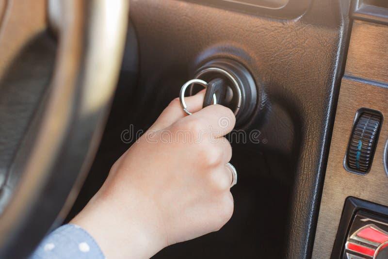 Kobiety ` s ręka na samochodowym ` s kluczu, próby zaczynać silnika, obraca dalej klucz w keyhole i toczy wewnątrz tło, auto ` s  obrazy stock