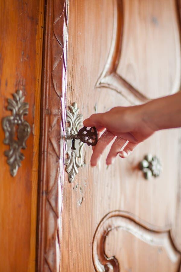 Kobiety ` s ręka otwiera duży starego, rocznik szafa obraz stock