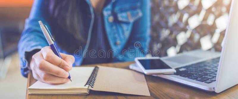 Kobiety ` s ręka pisze na notepad z piórem i telefonu wi zdjęcia stock
