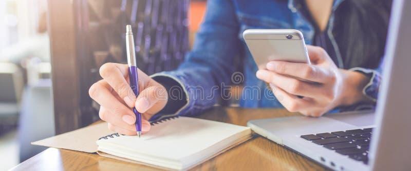 Kobiety ` s ręka pisze na notepad z piórem i telefonu wi fotografia royalty free