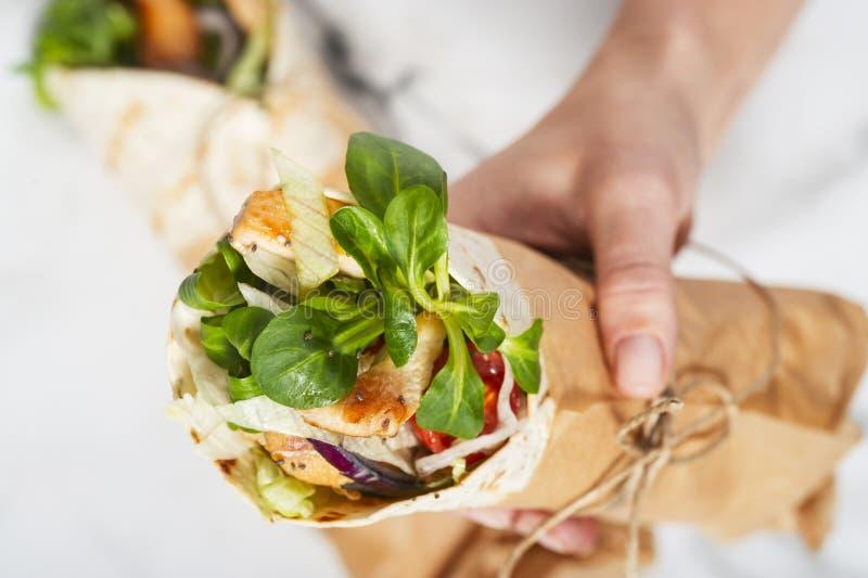 Kobiety ` s ręka trzyma świeży opakunek wiążę tortilla round z brown papierem i sznurkiem obraz stock