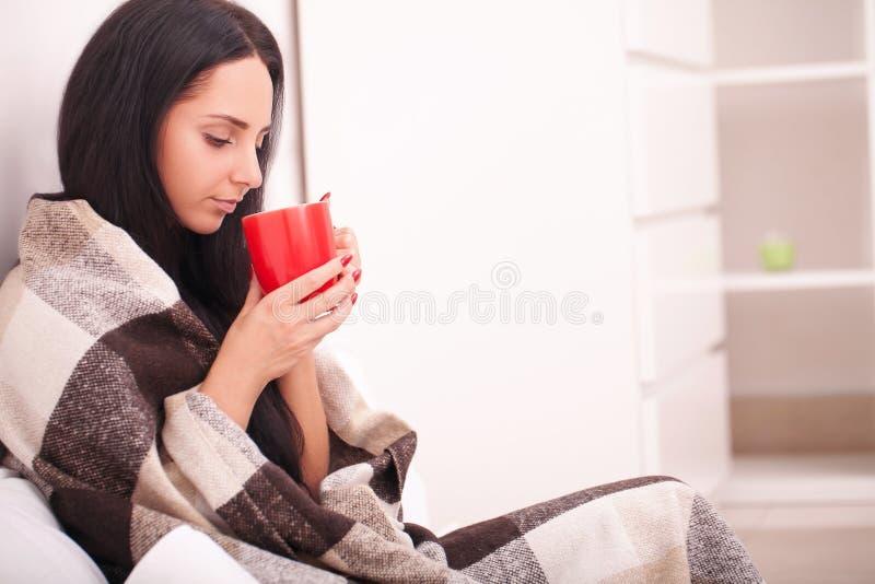 Kobiety ` s ręka trzyma czerwoną filiżankę kawy Z pięknym winte zdjęcia stock
