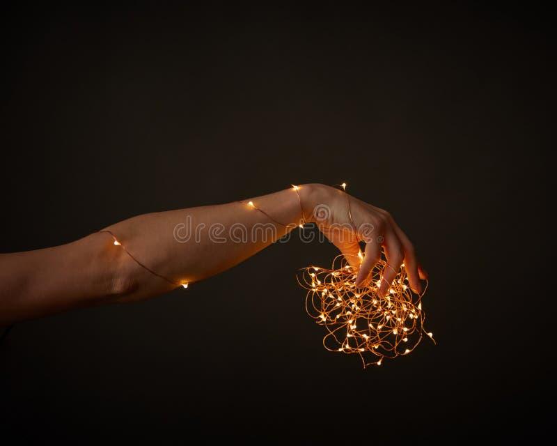 Kobiety ` s ręka trzyma jaskrawych bożonarodzeniowe światła na czarnym tle z przestrzenią dla teksta Boże Narodzenia zdjęcie stock