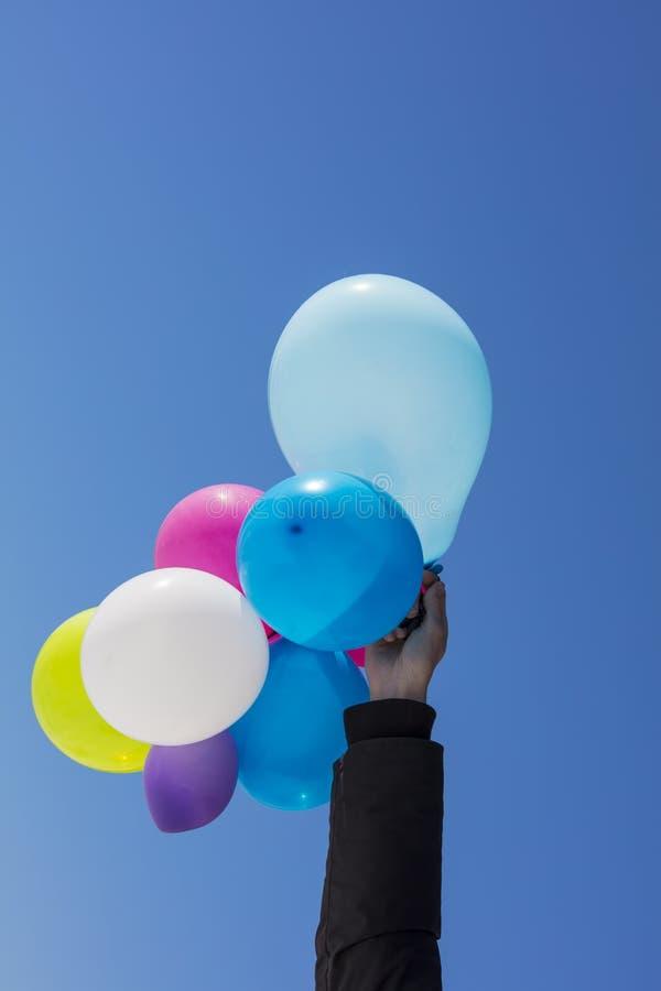 Kobiety ` s ręka trzyma kolorowych balony w powietrzu w Finlandia fotografia stock