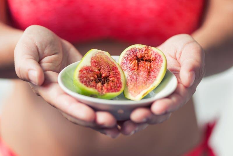 Kobiety ` s ręka trzymający dwa dojrzałej pokrojonej figi Kobieta w jaskrawym bikini z świeżą słodką egzotyczną owoc zdjęcie royalty free
