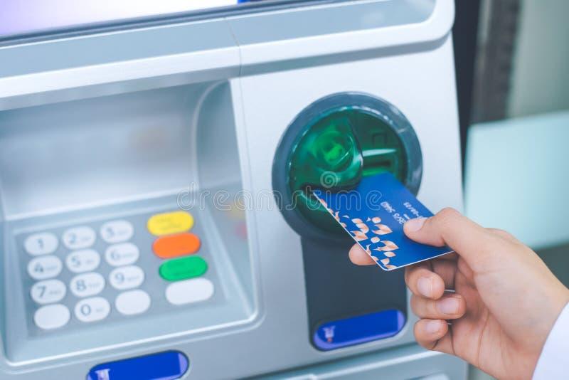 Kobiety ` s ręka wkłada kartę debetową w ATM zdjęcia stock