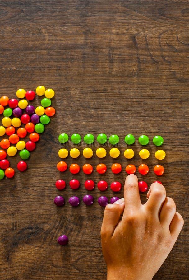 Kobiety ` s ręka zbiera nawet rząd kolorowi cukierki na drewnianym fotografia royalty free