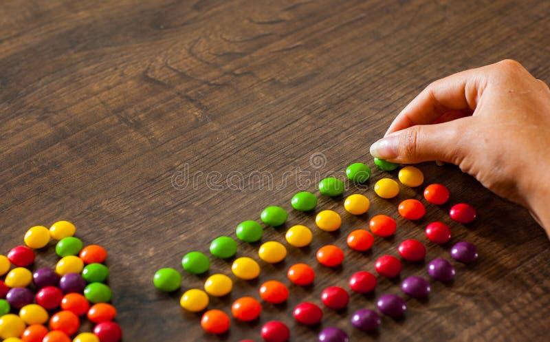 Kobiety ` s ręka zbiera nawet rząd kolorowi cukierki na drewnianym zdjęcie royalty free