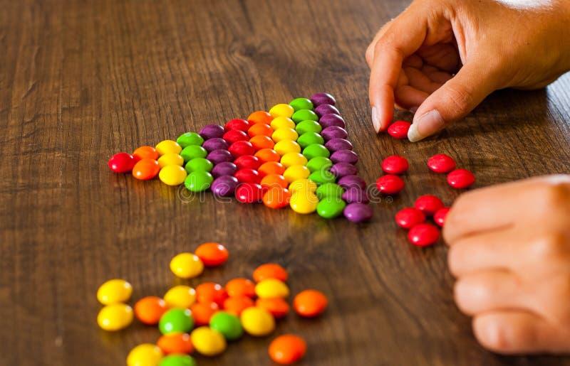 Kobiety ` s ręka zbiera nawet rząd kolorowi cukierki na drewnianym zdjęcia royalty free