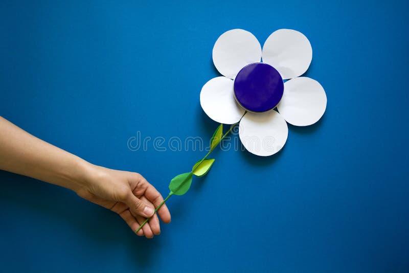 Kobiety ` s ręki trzyma papierowych kwiaty z kruszcowym kremowym słoju zbiornikiem na błękitnego papieru tle papieru cięcie obrazy stock