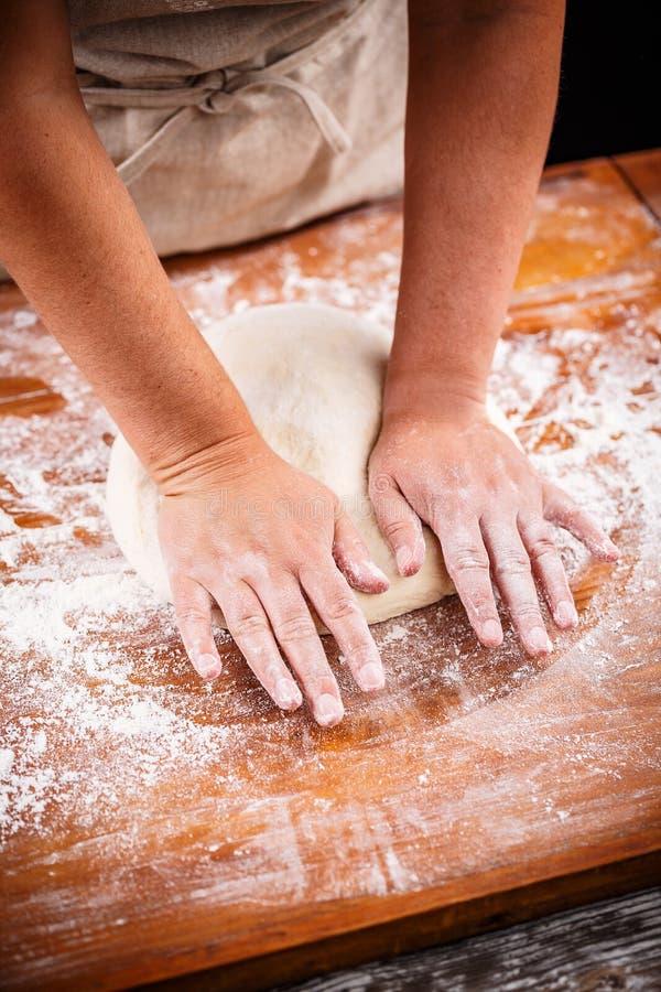 Kobiety ` s ręki ugniatają ciasto zdjęcie stock