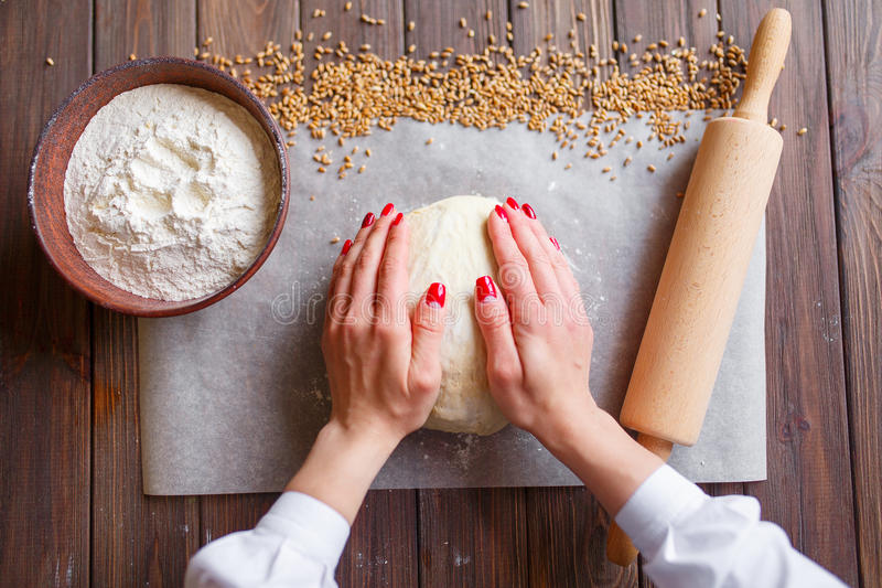 Kobiety ` s ręki ugniatają ciasto obraz royalty free