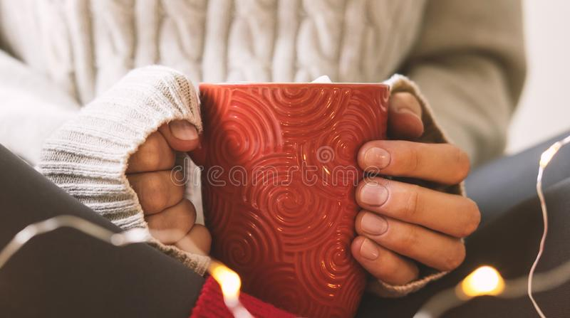 Kobiety ` s ręki w pulowerze trzymają filiżankę gorąca kawa, czekolada lub herbata, Pojęcie zimy wygoda, ranku pić, ciepły zdjęcie royalty free