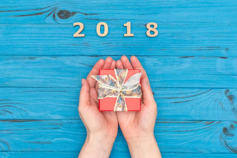 Kobiety ` s wręcza mienia prezenta pudełko blisko liczy 2018 na błękitnym starym stole zdjęcie stock