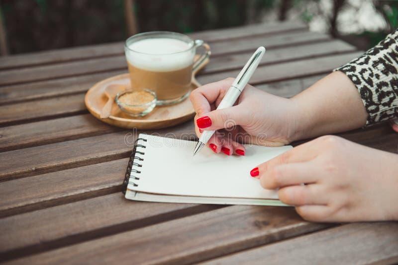 Kobiety ` s wręcza writing na notatniku, gorącej kawie i rocznika woode, obraz royalty free