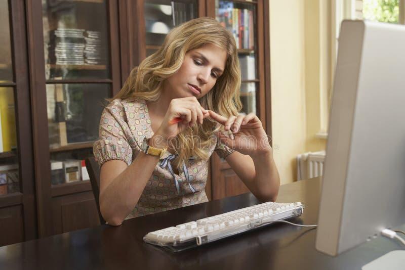 Kobiety segregowania paznokcie Nad komputerem W nauka pokoju obrazy stock