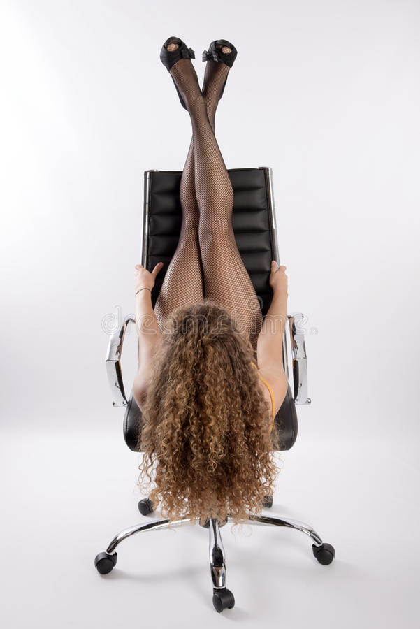 Kobiety siedzieć do góry nogami na biurowym krześle zdjęcie royalty free