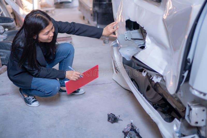 Kobiety sprawdzają samochody dla wypadków obraz royalty free