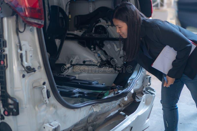 Kobiety sprawdzają samochody dla wypadków obrazy royalty free