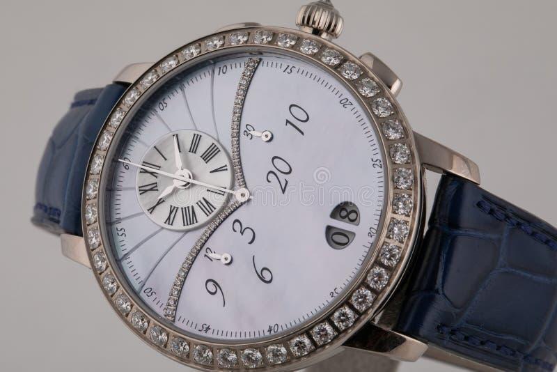 Kobiety srebny wristwatch z białą tarczą, osrebrza clockwise z chronografem na błękitnej rzemiennej patce odizolowywającej na bia zdjęcie stock