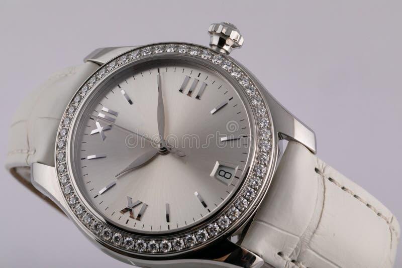 Kobiety srebra zegarek z jasnopopielatą tarczą, osrebrza clockwise, chronograf, z białą rzemienną patką odizolowywającą na białym fotografia royalty free
