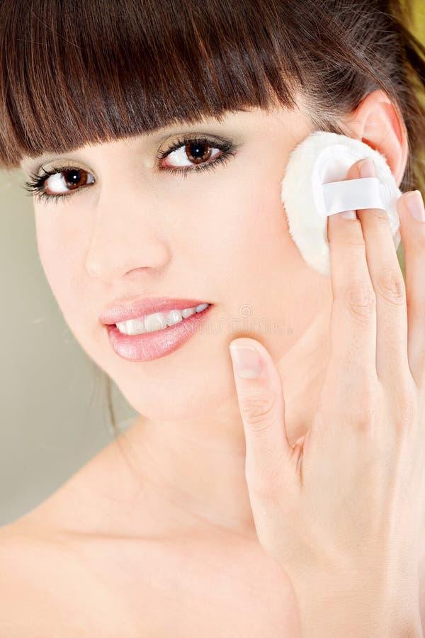 Kobiety stosować uzupełniał z kosmetyczną gąbką obraz stock