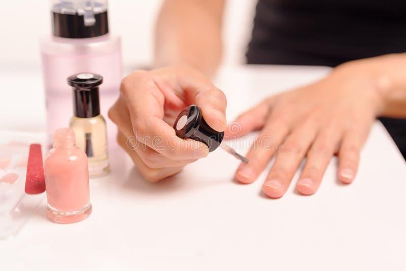 Kobiety stosuje gwoździa połysk na bielu stole z butelkami gwoździa połysk i pojęcie zmywacza, mody i piękna, zdjęcie royalty free
