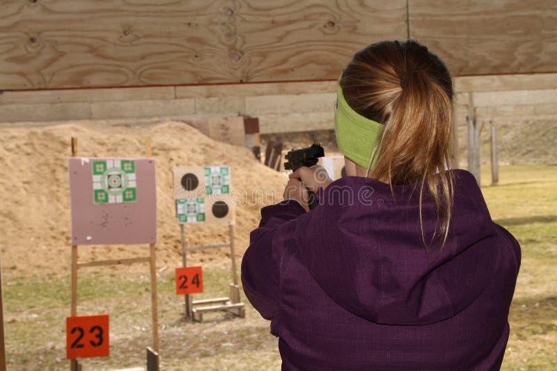 Kobiety strzelaniny cel przy pistoletowym mknącym pasmem obrazy stock